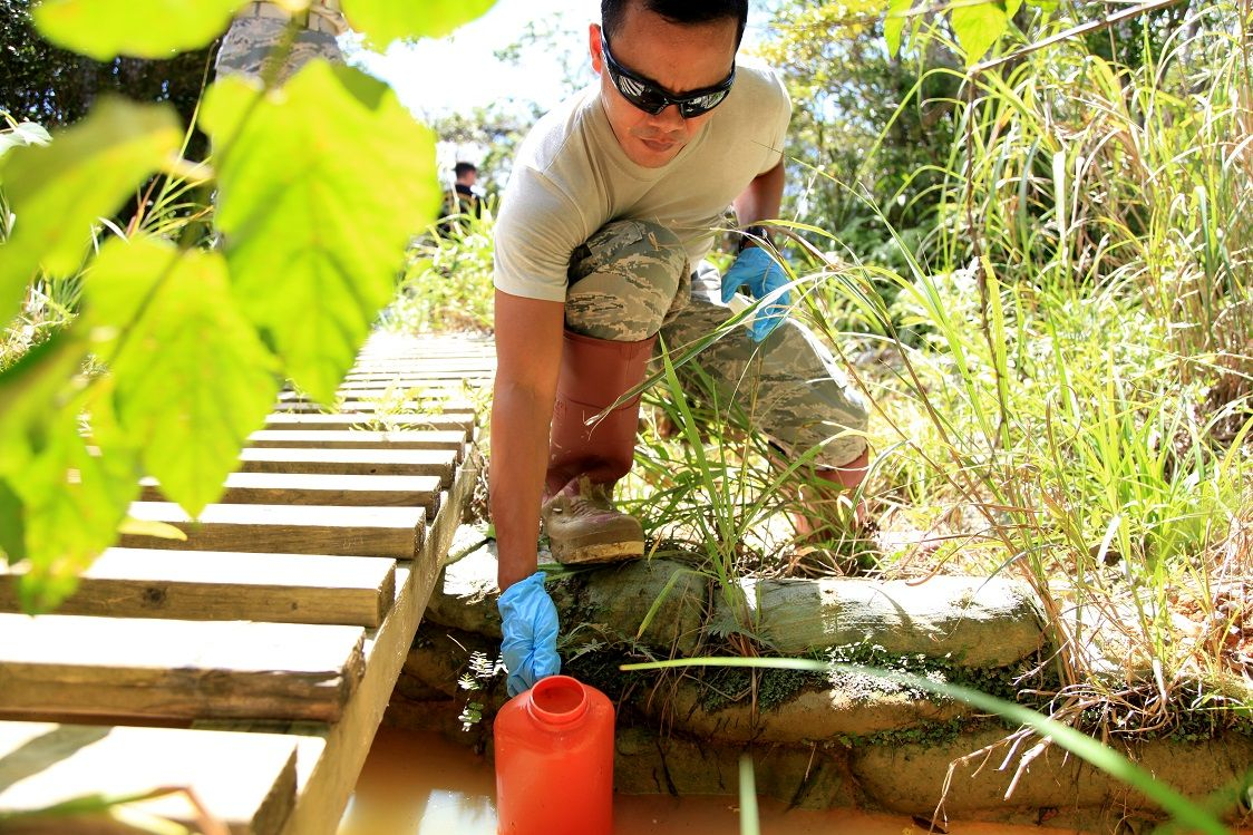 "Tech. Sgt. Donny Aspiras gathers a sample of water from the ""pit and pond"" obstacle Sept. 15."