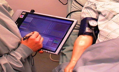 image of healthcare provider's arm and hand using the MTPAT software on a hand held tablet computer with a patient lying next to the provider. you can see the patients right arm with a blood pressure cuff on it.