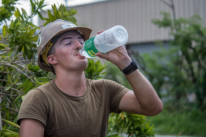Builder 3rd Class, assigned to Mobile Construction Battalion (NMCB) 1, detachment Guam, drinks water while reconstructing a roof for a home that was damaged during Typhoon Mangkhut. U.S. Navy photo by Mass Communication Specialist 2nd Class Kelsey J. Hockenberger)