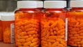 Image of several large prescription bottles filled with pills