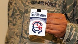 "Image of soldier holding up a badge that says ""Trusted Care."""