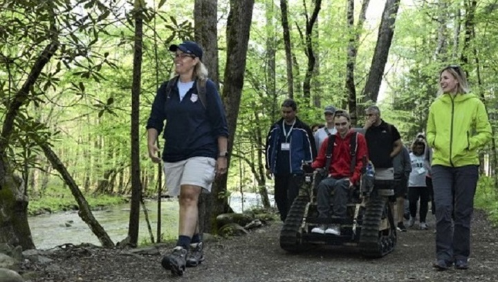 Group of people walking and on wheelchairs through the forest