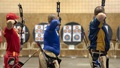 Three men shooting arrows at targets