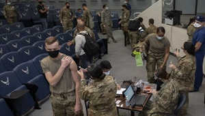 Military personnel wearing face mask standing in line to receive their COVID-19 Vaccine