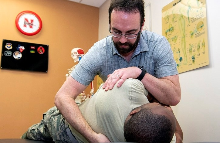 Chiropractor adjusting another man's back