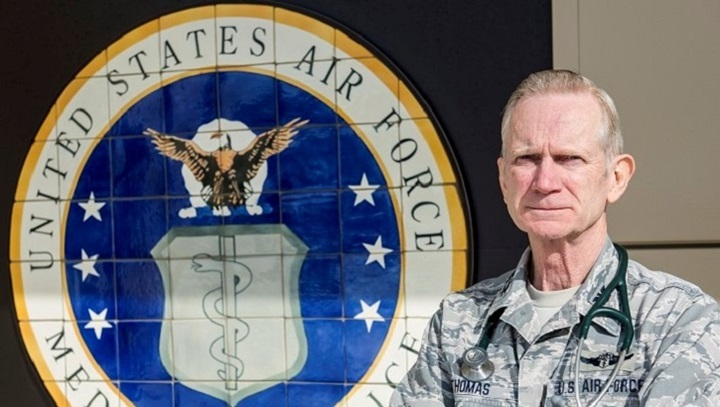 Uniformed officer standing next to an Air Force seal, wearing a stethoscope around his shoulders