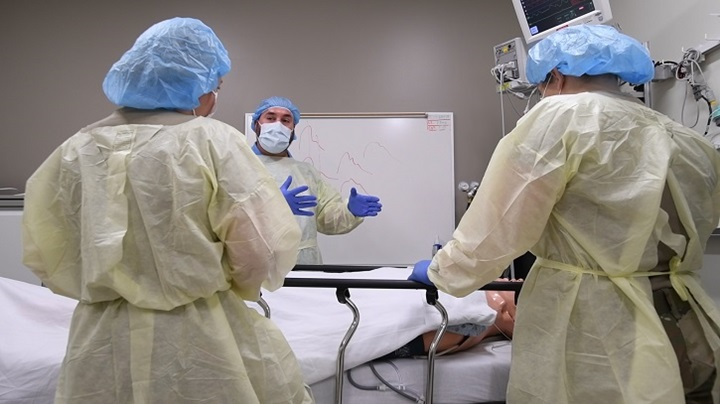 Three surgeons discussing a patient on an operating table