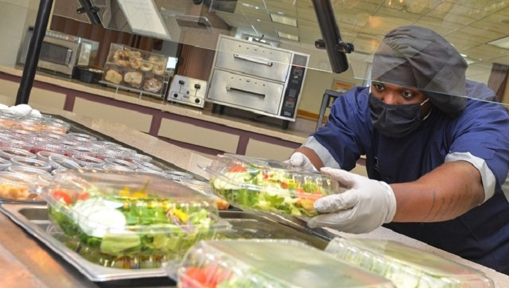 Man wearing mask and gloves putting container of salad into salad bar