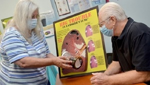 Woman showing man a poster about smoking cessation