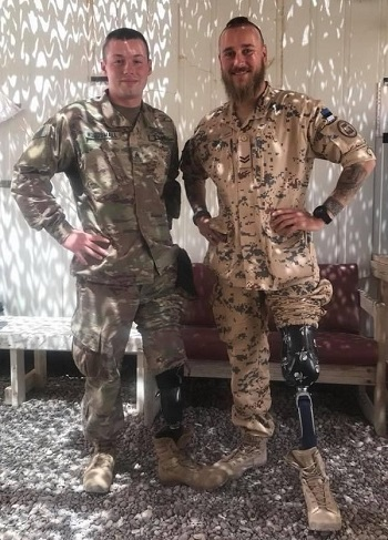 Two soldiers with leg amputations stand next to each other.