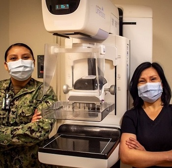 Two medical personnel wearing masks, standing next to a mammography machine