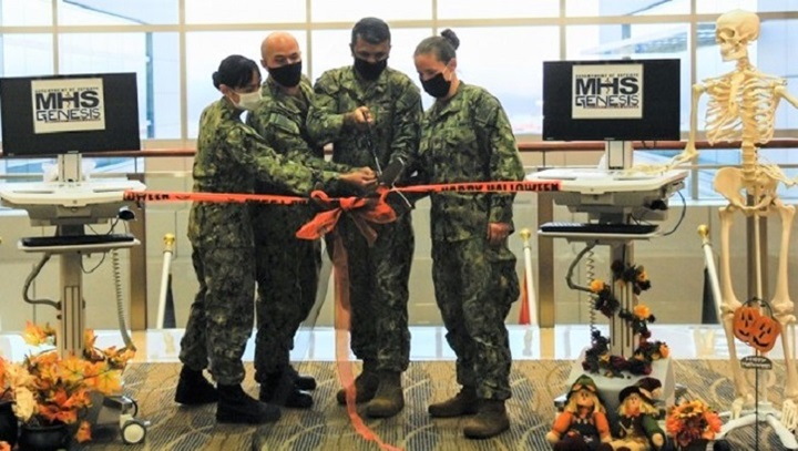 "Four military personnel, wearing masks, standing in front of two computer screens that say ""MHS GENESIS."""