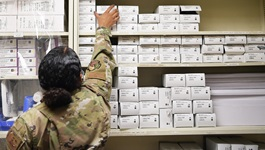 Military personnel in a supply room, reaching for the top shelf