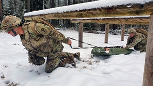 Soldiers in the snow, pulling a sled of materials