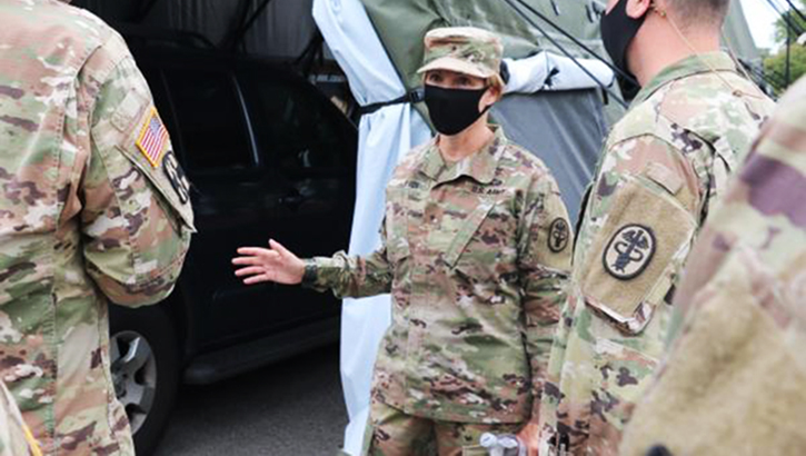 Soldier in mask speaking to other soldiers