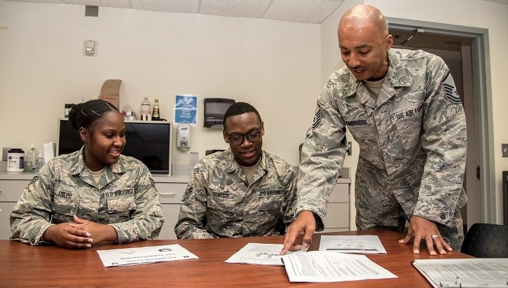 Three soldiers at a desk, two sitting and one standing, pointing at a piece of paper