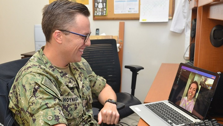 Military physician sitting at desk, talking to patient on his computer