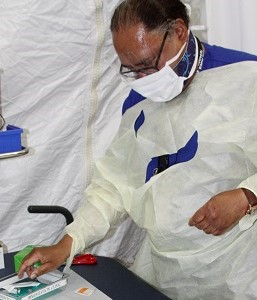 A nurse wearing a mask with needles in a tray
