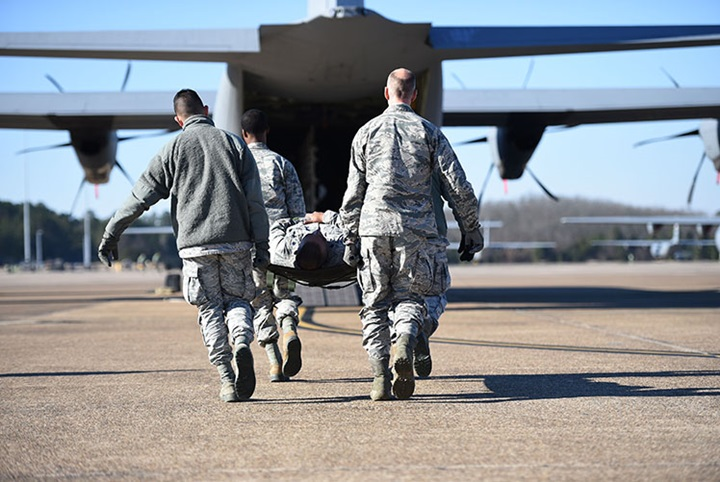 Airmen from the 19th Medical Group litter-carry a simulated patient onto a C-130J during an aeromedical evacuation training mission at Little Rock Air Force Base in 2019. (Photo Courtesy of U.S. Air Force)
