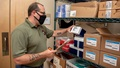 Man wearing mask checking inventory on shelves