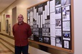 Sean Patterson, Armed Forces Medical Examiner System Department of Defense DNA Registry DNA analyst, stands in front of the USS Oklahoma History Board Nov. 29, 2016, at AFMES on Dover Air Force Base, Delaware. The board tells what happened to the USS Oklahoma during the attack on Pearl Harbor and the difficulty of identifying the 429 service members who were lost. (U.S. Air Force photo/Senior Airman Ashlin Federick)