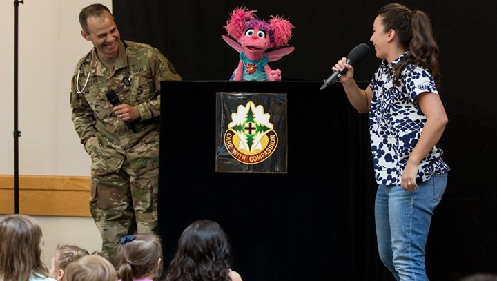 Army Col. (Dr.) Matthew Studer, the chief of Madigan's Department of Pediatrics, talks with Nina and Abby Cadabby from Sesame Street during a special visit at Madigan Army Medical Center on July 26. (U.S. Army photo by Ryan Graham)