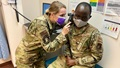 Military health personnel checking the ears of a patient