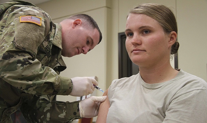 Army Pvt. Jonathan Bowen (left), health care specialist with the 1st Special Troops Battalion, 1st Cavalry Division Sustainment Brigade, provides an influenza vaccination to another Soldier.