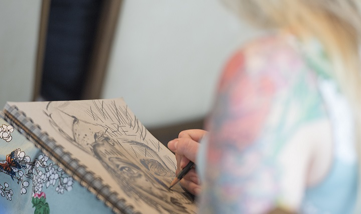 Air Force veteran Adrianna Ruark works on a drawing. (DoD photo by Roger L. Wollenberg)