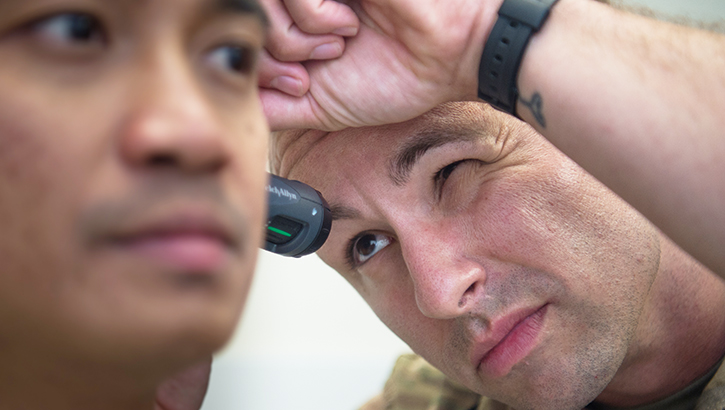 A doctor looking into a soldier's ear