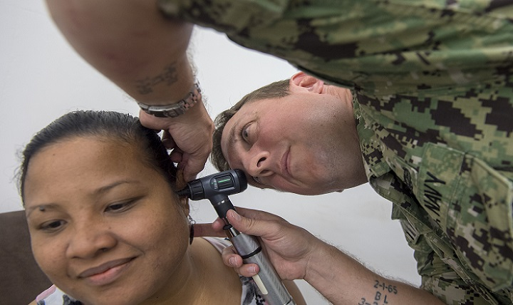 Navy Lt. Matt Thomas, an audiologist supporting Pacific Partnership 2018, examines a patient's ear during a community health fair at Yap Memorial Hospital in Micronesia. (U.S. Navy photo by Petty Officer 1st Class Byron Linder)
