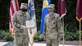 Two masked soldier display an award in front of flags.