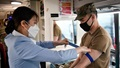 Military personnel wearing a face mask drawing blood during a blood drive