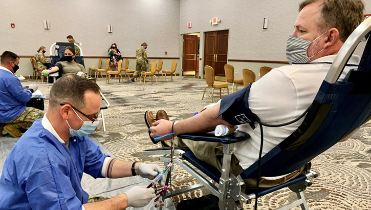 Man wearing mask, giving blood