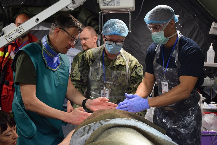 Navy Cmdr. Mark Lambert (center) and Navy Hospital Corpsman 2nd Class Amos Bogs (right), work with Capt. Peter Landell (left), Swedish Armed Forces, during a multinational medical drill, Cincu Military Base, Romania, during exercise Vigorous Warrior 19. (U.S. Air Force photo by 1st Lt. Andrew Layton)