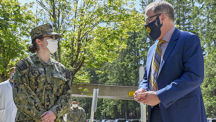 Man in mask presents military coin to female soldier
