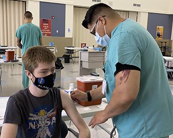 A teen boy gets the COVID-19 vaccine.