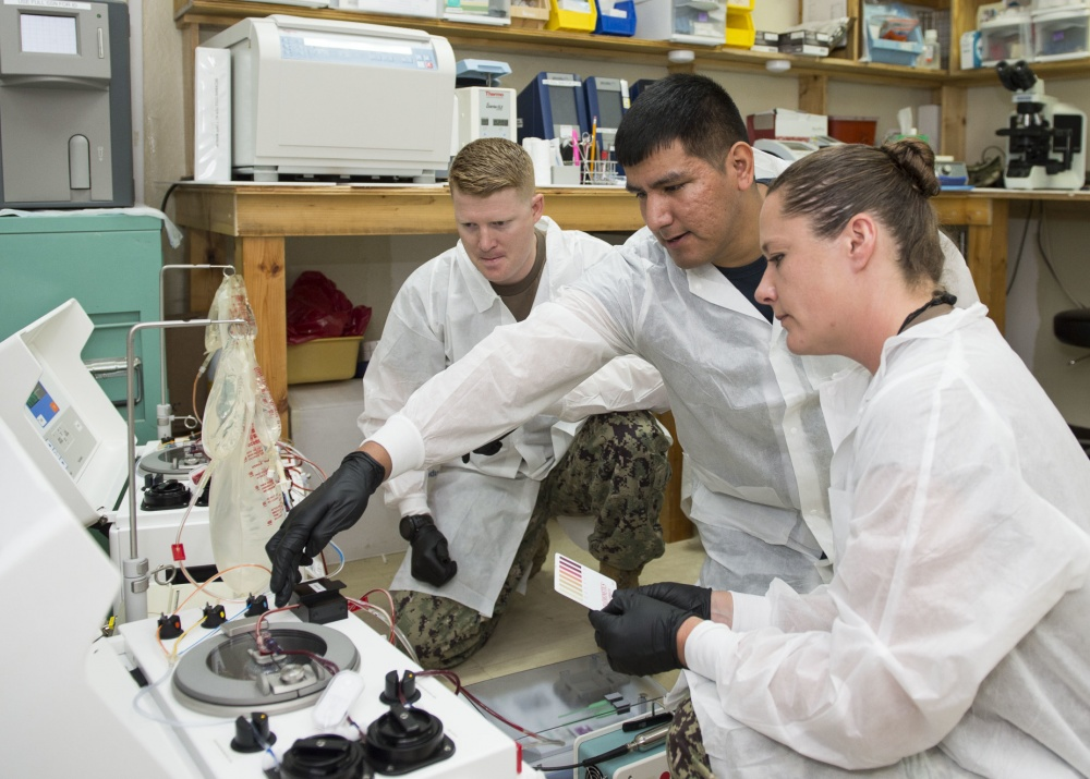 Hospital Corpsmen 2nd Class Andrew Kays (right) and Christi Greenwood (left), deployed with the Expeditionary Medical Facility at Camp Lemonnier, receive training on the Automated Cell Processor 215 while Hospital Corpsman 2nd Class Joshua Paddlety from Naval Hospital Sigonella, Italy, as part of implementation of the Frozen Blood Program here, March 13, 2019. (U.S. Navy photo by Mass Communication Specialist 1st Class Joe Rullo)