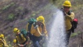 Men in protective suits dousing a flame with water from a hose