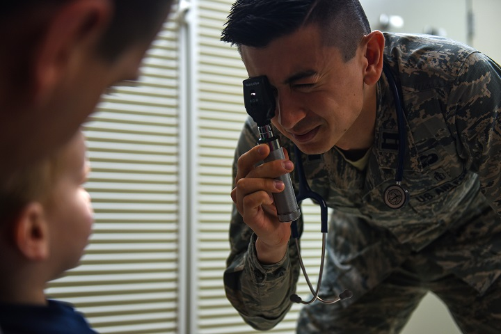 Air Force Capt. Joseph Migliuri, 92nd Medical Group pediatrician, performs a wellness vision exam during a patient's check-up at Fairchild Air Force Base, Washington. The pediatric team has implemented a new concept of operations: rewarding, efficiency, setting priorities and empowering team members, or RESET, to their system of patient care. The integration of RESET in the Military Health System Genesis workflow has improved the clinic's goals of patient access and care. (U.S. Air Force photo by Airman 1st Class Whitney Laine)