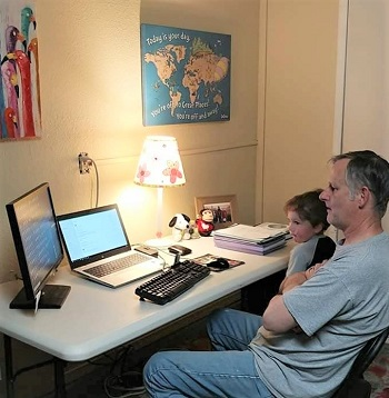 Image of man sitting at desk with son on his lap