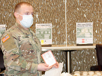 Military personnel wearing a face mask giving a presentation on food options