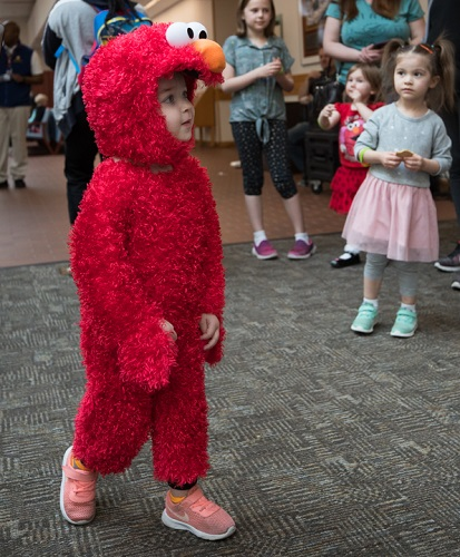 A child, dressed as Sesame Street's Elmo, visited Madigan Army Medical Center April 1 to get a photo with the beloved character. (U.S. Army photo by Ryan Graham)
