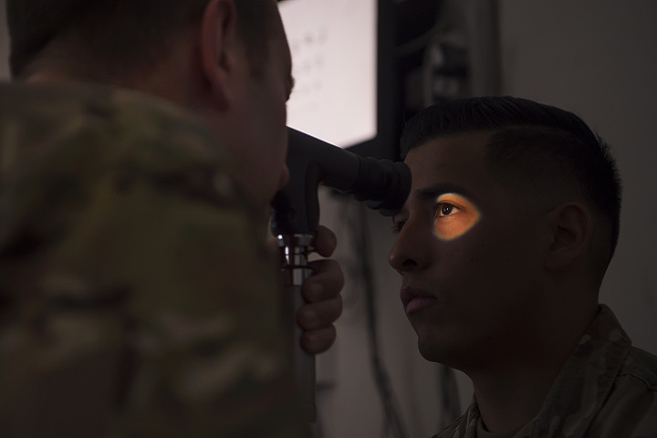 Air Force Lt. Col. Peter Carra, 379th Expeditionary Medical Group optometry officer in charge, performs an eye exam for a Soldier at Camp As Sayliyah, Qatar. (U.S. Air Force photo by Tech. Sgt. Christopher Hubenthal)