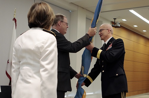 Assistant Secretary of Defense for Health Affairs Tom McCaffery (center), passes the colors to the new DHA director, Army Lt. Gen. Ronald Place (right), as Navy Vice Adm. Raquel Bono, the outgoing director of the Defense Health Agency, watches. (MHS photo)