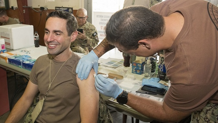 Navy Hospital Corpsman 2nd Class Alexander Wrigel (right), a medic assigned to Task Group 68.6, forward deployed to Camp Lemonnier, administers a flu shot to Navy Lt. Cmdr. Hector Ubinas. (U.S. Navy photo by Mass Communication Specialist 1st Class Joe Rullo)