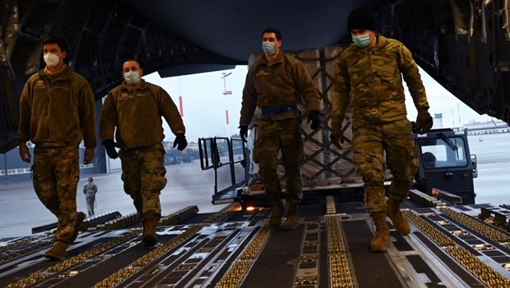 Picture of military personnel wearing face masks walking into an aircraft