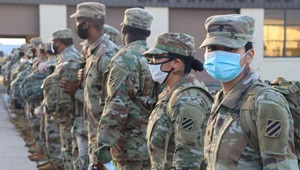 Soldiers standing in a line, wearing masks