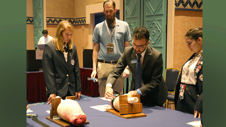 USU's Dr. Craig Goolsby (center) observes as high school students at a conference in Orlando, Florida, practice using a tourniquet after watching a web-based tutorial. Goolsby is researching effective teaching methods as part of a grant to develop a trauma first-aid course for students that incorporates elements of Stop the Bleed. (USU photo by Sarah Marshall)