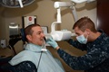 Navy Dental Assistant Petty Officer 3rd Class Donald Kern positions the digital X-Ray tubehead, or camera, next to his patient's jaw for bitewing X-rays as part of an annual dental exam at Tinker Air Force Base. (U.S. Air Force photo/Staff Sgt. Lauren Gleason)